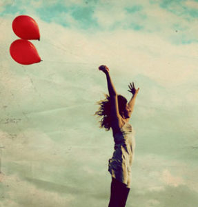 This is an image of a woman letting go of two red balloons.