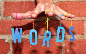 A hand with the letters spelling words hanging from the fingers